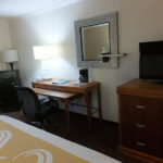 room amenities including a TV, dresser, work desk with chair, microwave and mini fridge